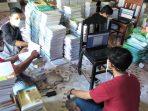 Para relawan ALC sedang sibuk melakukan proses penempelan barcode dan entri koleksi