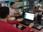 para relawan ALC sedang melakukan entri koleksi perpustakaan kedalam sistem